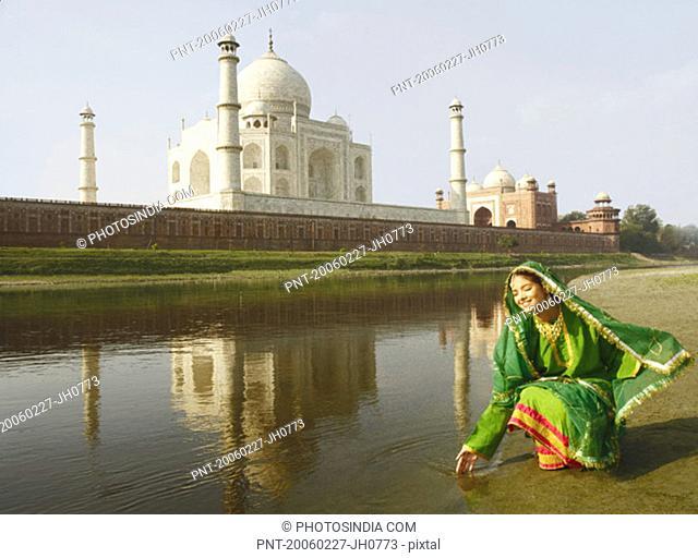 Young woman crouching on the riverbank, Taj Mahal, Agra, Uttar Pradesh, India