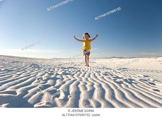 Girl walking on dune, White Sands National Monument, New Mexico, USA