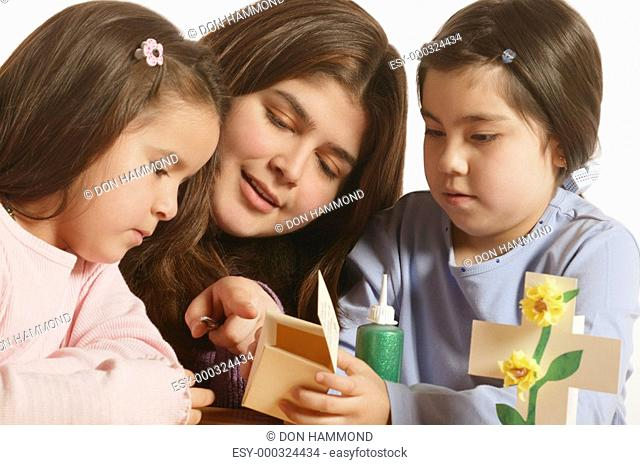 Two young girls being instucted on craftmaking