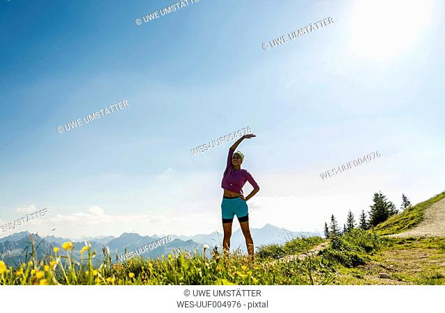 Austria, Tyrol, Tannheim Valley, young woman exercising in mountains
