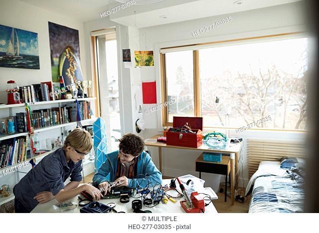 Boys assembling circuit board in bedroom