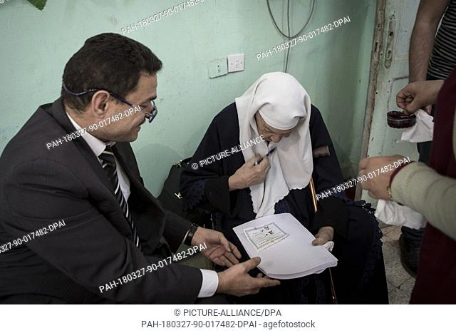 An elderly Egyptian woman fills out her ballot on the second day of the 2018 Egyptian presidential electionsat a polling station, in Giza, Egypt, 27 March 2018