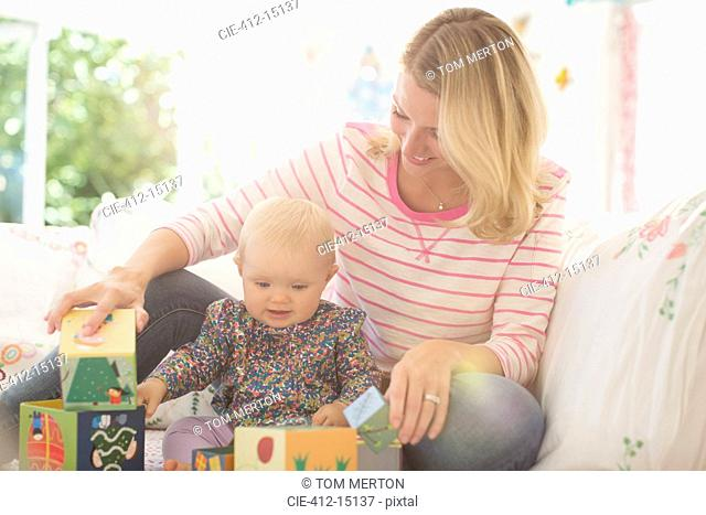 Mother and baby girl playing with blocks