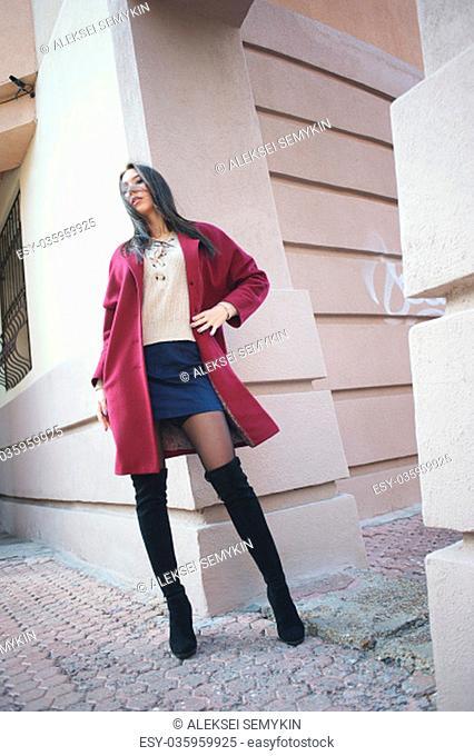 young beautiful stylish woman walking in burgundy coat, street style, spring summer trend, dark skirt, beige jacket, flirty
