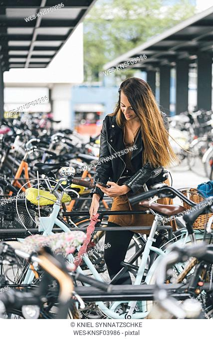 Young woman with bicycle using cell phone in the city