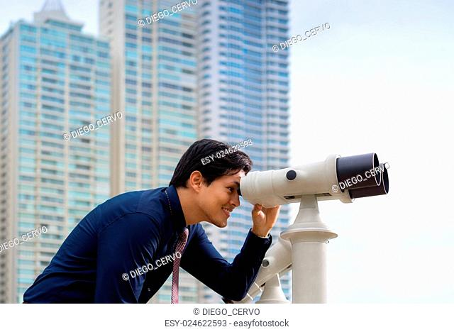Portrait of young chinese business man standing in Panama City and looking through binoculars. Concept of forecasting, career, success