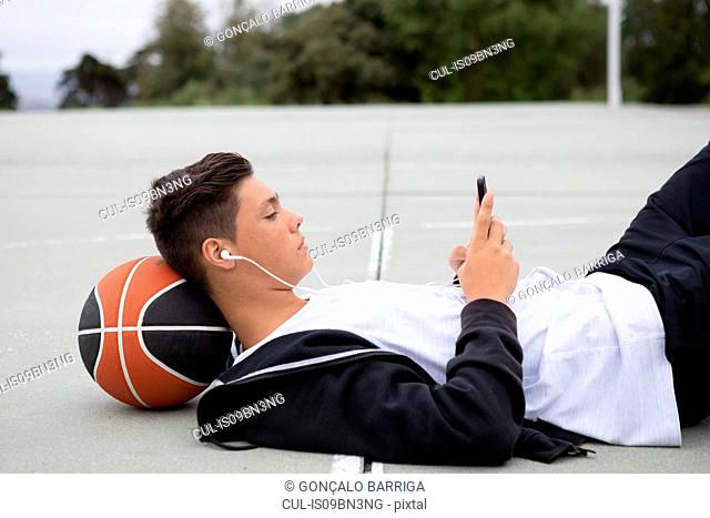 Male teenage basketball player lying on basketball court looking at smartphone