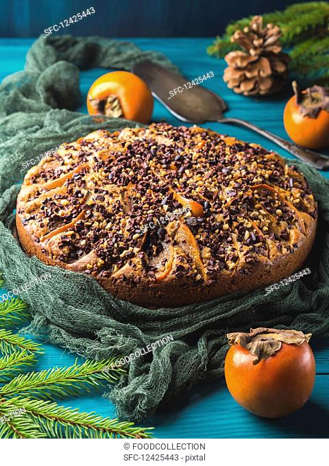 Whole wheat cake with persimmons topped with raw cocoa nibs and walnuts