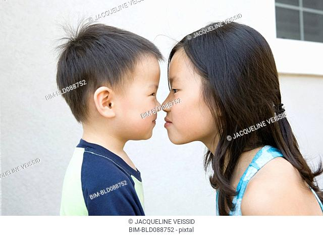 Chinese brother and sister staring at one another