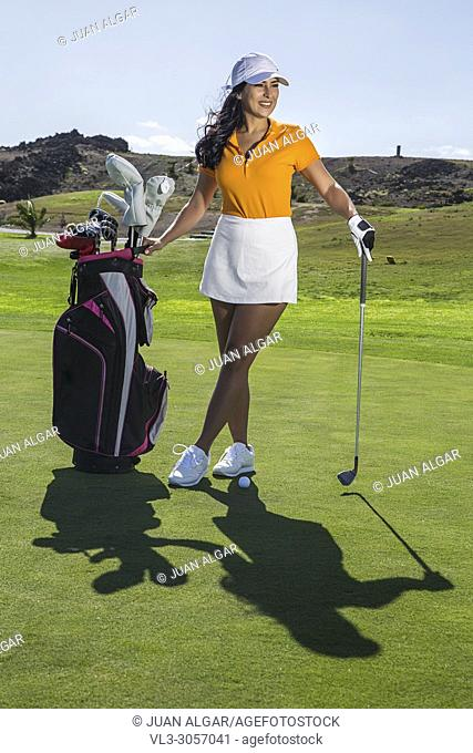 Beautiful elegant model wearing stylish outfit for golf game and standing with bag of drivers on green field