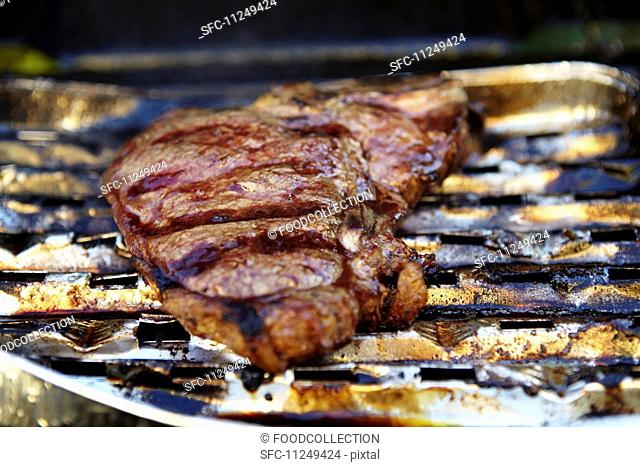 A T-bone steak in an aluminium tray on a barbecue (close-up)