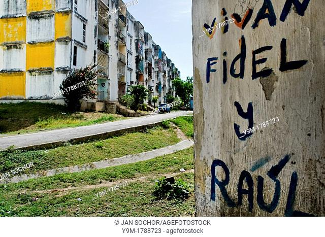 A writing, supporting the regime of Fidel Castro and his brother Raul Castro, painted on the wall of a concrete apartment block in the neighbourhood of Abel...