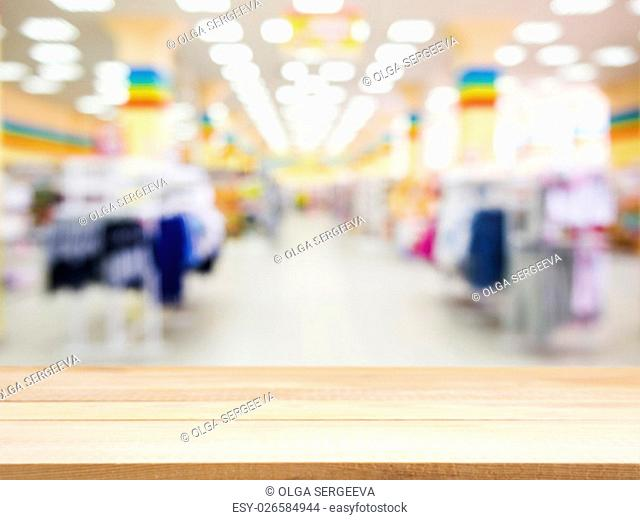 Wooden board empty table in front of blurred background. Perspective light wood over blur in kids wear store - can be used for display or montage your products