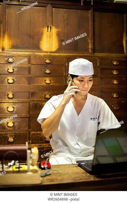 A small artisan producer of specialist treats, sweets called wagashi. A cook using a laptop and making a phone call at a desk