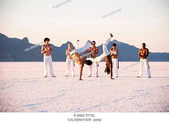 Team clapping man performing capoeira on Bonneville Salt Flats, Utah, USA