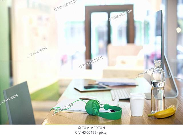 Headphones, water bottle, coffee and banana on desk with computer