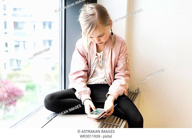Girl (8-9) using mobile phone