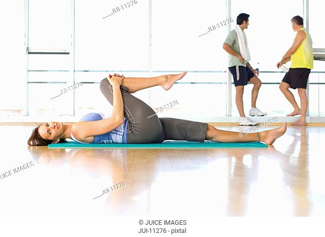 Woman doing yoga in exercise studio, men in background