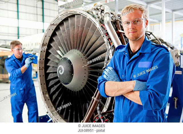 Close up portrait of confident engineer standing next to engine of passenger jet in hangar