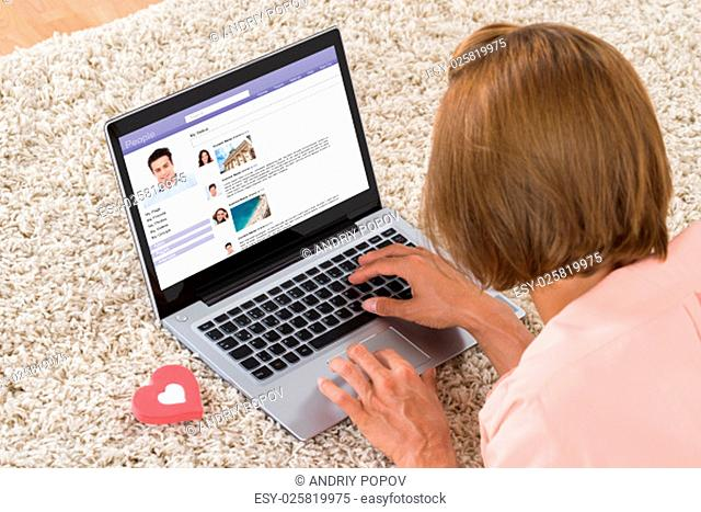 Close-up Of Woman With Heart Sign Chatting On Social Networking Site On Laptop