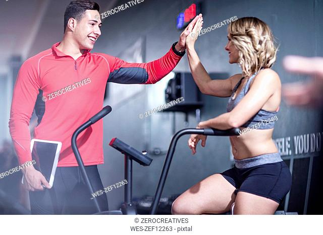 Fitness instrustor high fiving with woman on exercise machine