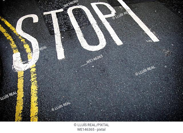 Stop sign painted on pavement, with double yellow line