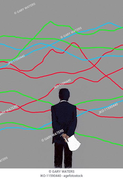 Businessman contemplating confusing line graph