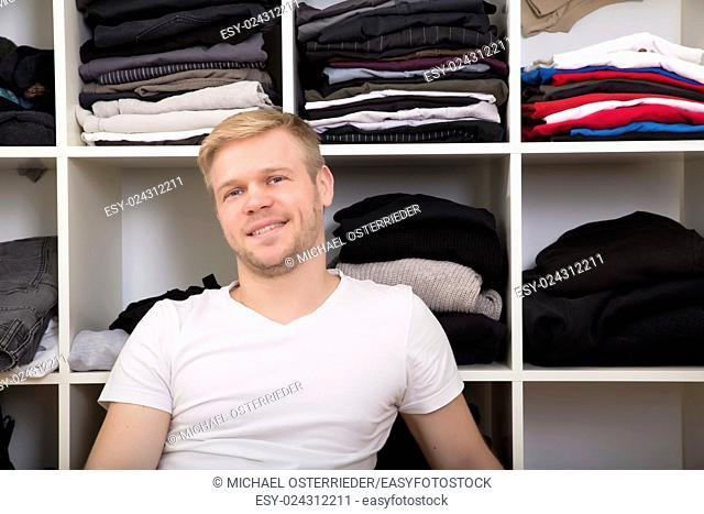 Young man sitting in front of his wardrobe
