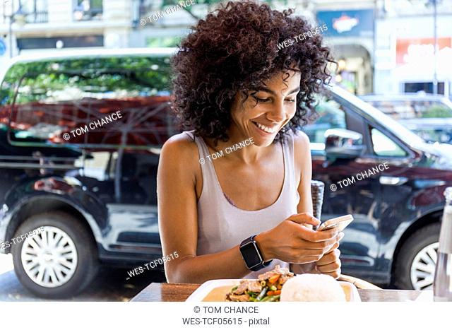 Portrait of smiling young woman with sitting at pavement restarant looking at cell phone