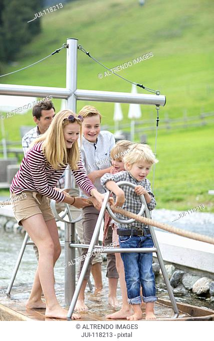 Father And Children Playing On Wooden Raft In Adventure Park