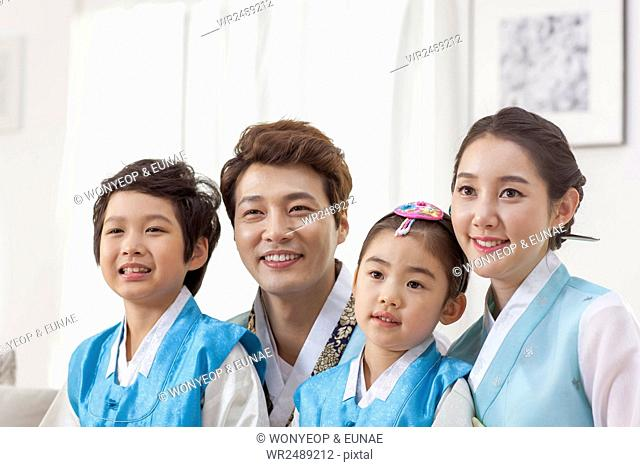 Portrait of smiling Korean family in traditional Korean clothes