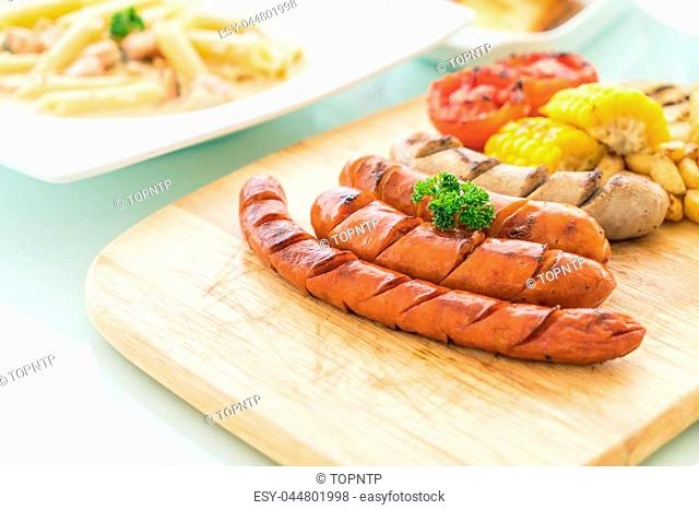 mix grilled sausage with vegetables and french fries on wood board