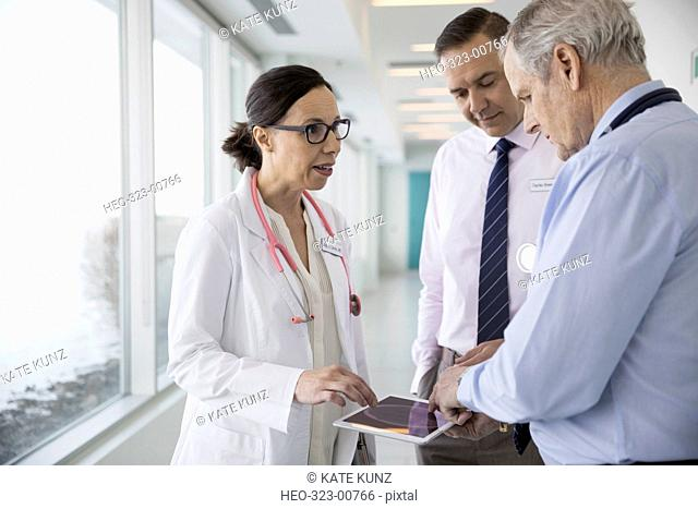 Doctors consulting, reviewing digital x-ray on digital tablet in clinic corridor