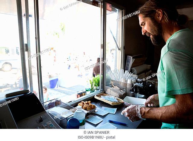 Man preparing order in fast food trailer