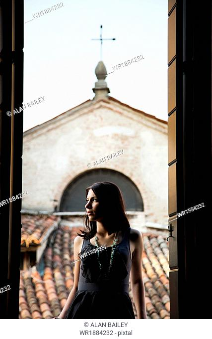 Italy, Venice, Young woman standing in balcony door, contemplating view
