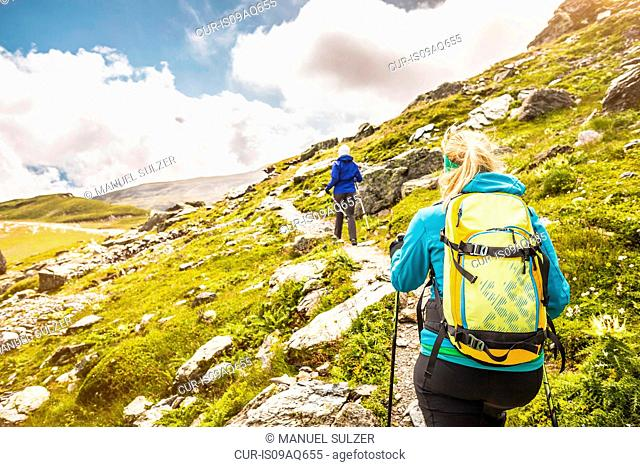 Two female hikers hiking up path, Fil de Cassons, Segnesboden, Graubunden, Switzerland