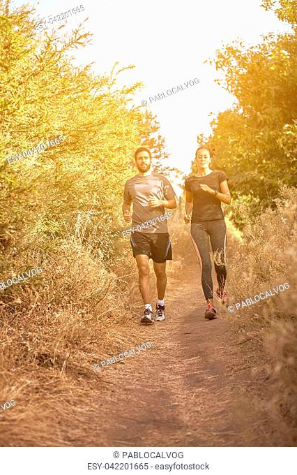 Young couple running down a mountainpath in the late afternoon sunshine with trees behind, while wearing casual clothing