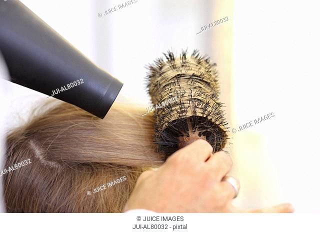 Close up of hair stylist blowdrying clientis hair with round brush