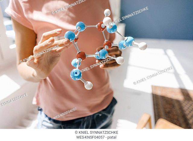 Female scientist holding molecule model