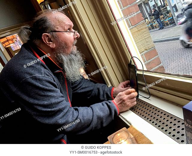 Tilburg, Netherlands. Elder man parking his tablet computer in a window, just above an electrical outlet, thus recharging the lectrical device