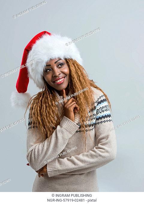 Christmas Santa hat woman portrait. Pensive happy girl on gray background