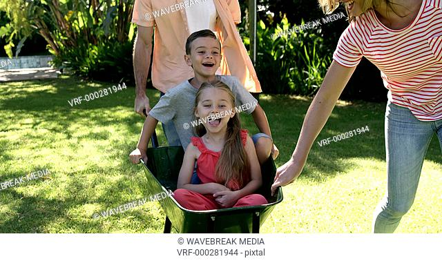 Portrait of cute family playing with the wheelbarrow in the garden