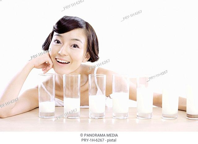 Young fashionable woman and seven glasses of milk
