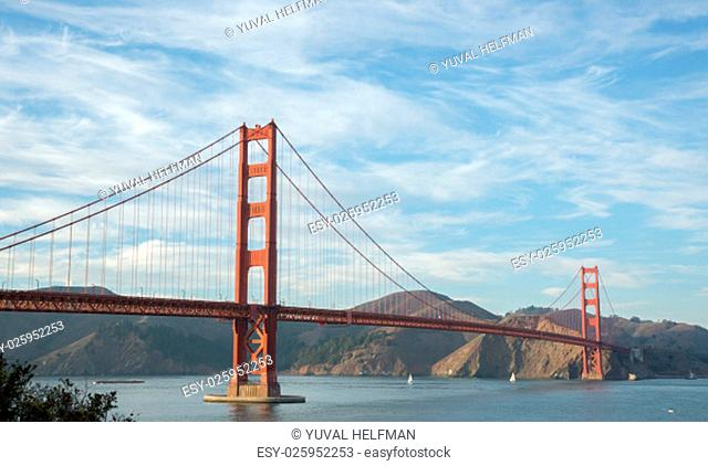The Golden Gate Bridge beneath a blue sky with wispy clouds on a lovely afternoon