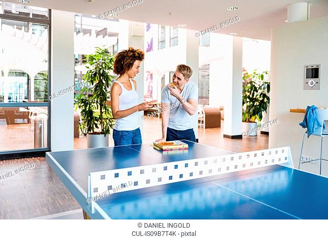 Young woman and boyfriend eating pizza at apartment table tennis table
