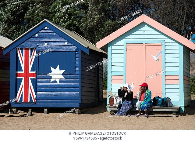 People sitting on the steps of the Victorian-era bathing boxes at Brighton Beach on the shores of Port Phillip Bay, Melbourne, Australia