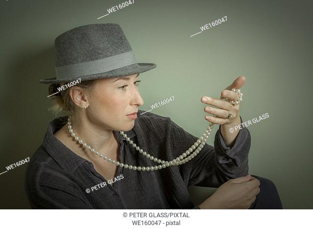 Young woman examining her pearl necklace and wearing a man's hat