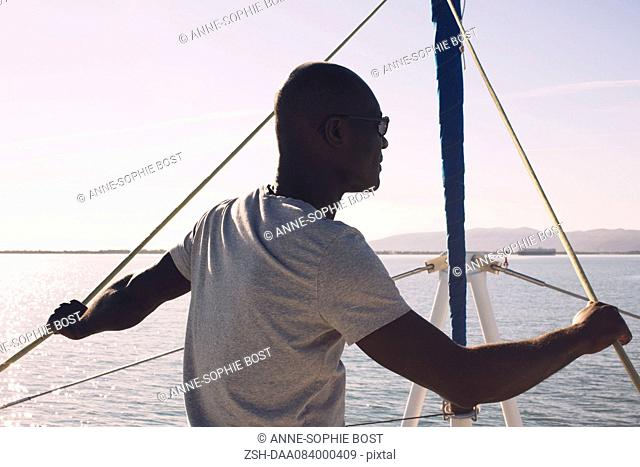 Man on sail boat, looking at view