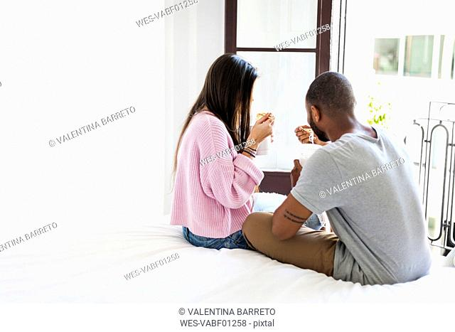 Couple sitting on bed, eating Chinese noodles