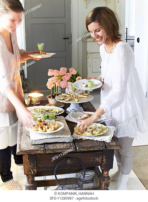 A festive buffet with various canapés on a rustic wooden table and young women with plates